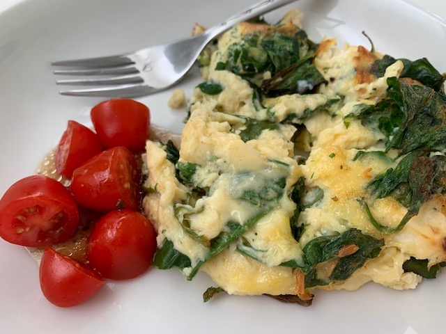 Spinach and Feta Fritatta On A Plate Served With Tomatoes.