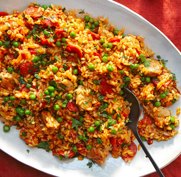 Paella In A White Bowl. Paella Is A Spanish Rice Dish With Chicken, Chorizo And Prawns.