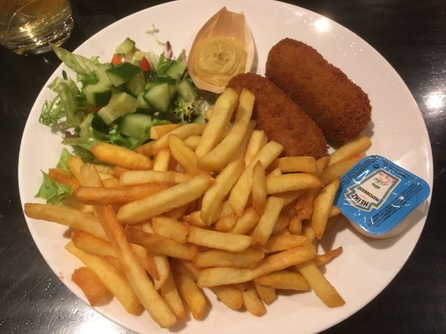 Kroket. Traditional Food From The Netherlands. Served With Chips And Salad On A White Plate.