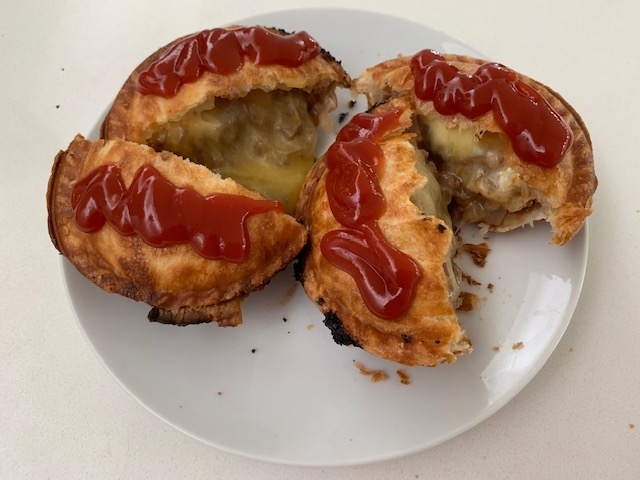 Round Meat Pie With Mince And Cheese Melted Inside. Cut In Half And Smothered With Tomato Sauce.